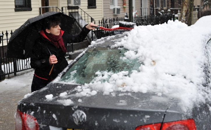 Emily Andeasini, of Brooklyn, New York, cleans snow off of her car in Brooklyn, New York, USA, on 29 October 2011. A large storm is delivering an early snow fall to the northeastern part of the United States.  EPA/JUSTIN LANE