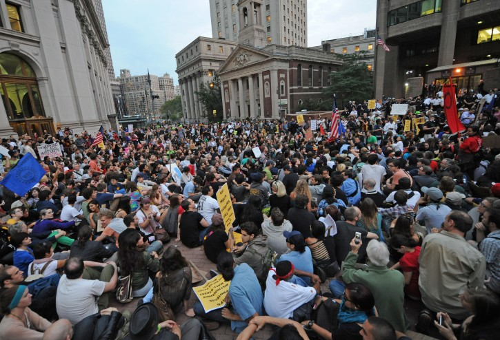 "Protestors sit in the plaza of Police Headquarters, Friday, Sept. 30, 2011, in New York.  The ""Occupy Wall Street"" protest is in its second week, as demonstrators speak out against corporate greed and social inequality. (AP Photo/ Louis Lanzano)"