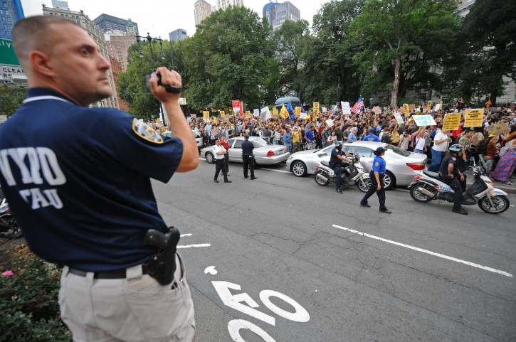 "An officer videotapes a several block long march up Broadway towards Police Headquarters, Friday, Sept. 30, 2011, in New York. The ""Occupy Wall Street"" protest is in its second week, as demonstrators speak out against corporate greed and social inequality.  (AP Photo/ Louis Lanzano)"