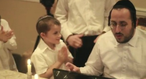 In this image grab from the YouTube clip shows Lipa signing the petition with Rubashkin's children looking on
