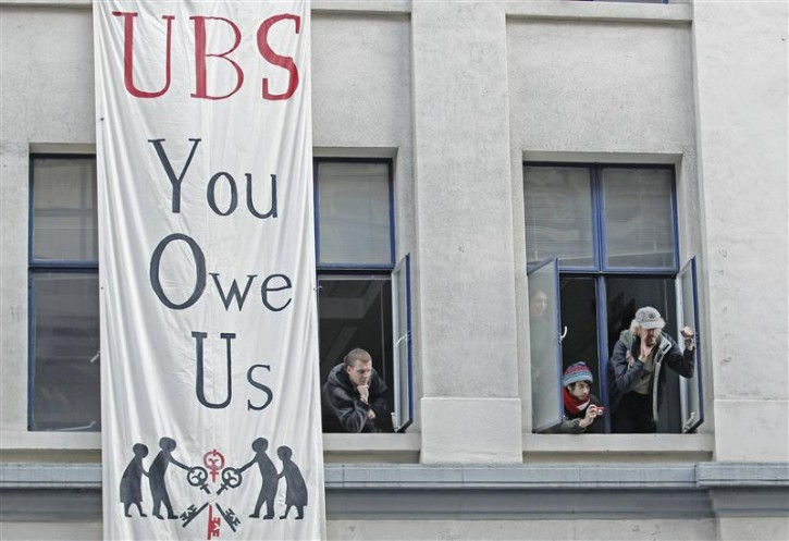 Protesters from the Occupy movement stand at the windows of one of several buildings in a quadrangle owned by banking giant UBS in the financial district City of London November 18, 2011.    REUTERS/Luke MacGregor