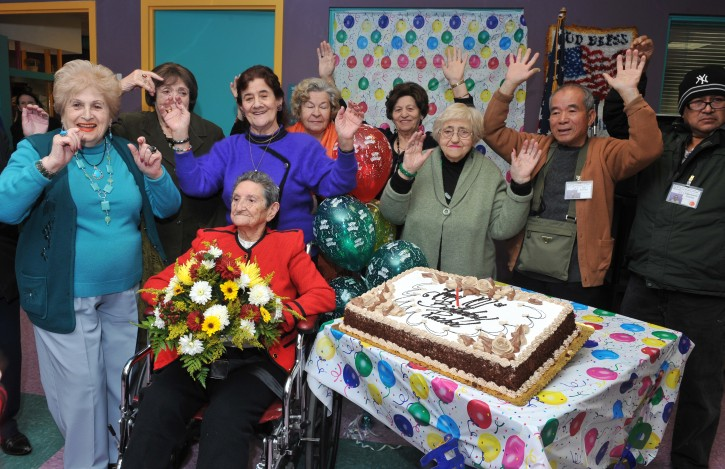 birthday girl! Seated, MJHS Adult Day Health Center participant Rachel Walfish is cheered by some of her closest friends, after having just accepted a gorgeous bouquet and presented a cake big enough for 101 candles.