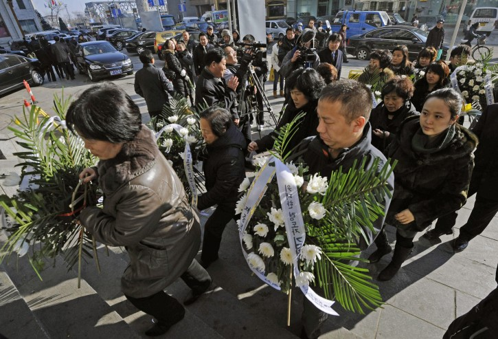 People carrying the condolence wreaths for late North Korean leader Kim Jong Il visit a branch of the North Korean general consulate in Dandong, China, Tuesday, Dec. 20, 2011. North Korea's leader Kim Jong Il died Saturday of a massive heart attack brought about by overwork and stress, according to the North's media. (AP Photo/Kyodo News)