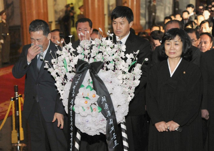 Mourners cry in front of the body of North Korean leader Kim Jong Il, not in photo, laid in a memorial palace in Pyongyang, North Korea, Tuesday, Dec. 20, 2011. (AP Photo/Kyodo News)
