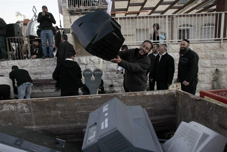 An ultra-Orthodox Jewish man throws a television screen into a garbage receptacle during a protest against what the religious demonstrators say is the broadcasting of immoral content by the Israeli Broadcasting Authority, outside one of the broadcaster's studios in Jerusalem December 6, 2011. REUTERS/Baz Ratner
