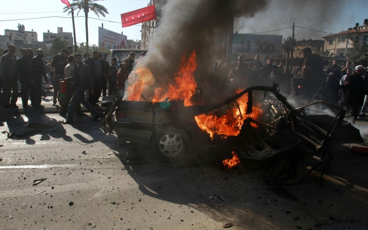 Palestinians gather around the wreckage of a car targeted in an airstrike in Gaza City, Thursday, Dec. 8, 2011. Two suspected Islamic militants were killed in an Israeli missile strike on their vehicle near a crowded public park in Gaza City on Thursday, a Palestinian health official said. Israel's military had no immediate comment. AP/PTI