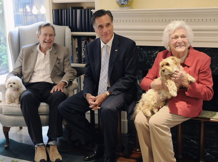 Republican presidential candidate, former Massachusetts Gov. Mitt Romney, center, visits with former President George H.W. Bush, his wife Barbara and their dogs Mimi and Bibi, Thursday, Dec. 1, 2011, at their home in Houston. (AP Photo/Pat Sullivan)