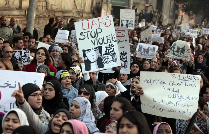 Hundreds of Egyptian women march at Cairo streets as they angered by the recent violence used against them in clashes between police and protesters in Cairo, Egypt Tuesday, Dec. 20, 2011. Egypt's ruling generals are coming under mounting criticism at home and abroad for the military's use of excessive force against unarmed protesters, including women, as they try to crush the pro-democracy movement calling for their ouster. Arabic at right read, in Jan. 25, we demand bread, freedom and dignity, and until now we have  human rights violations and violence against women.  (AP Photo/Amr Nabil)