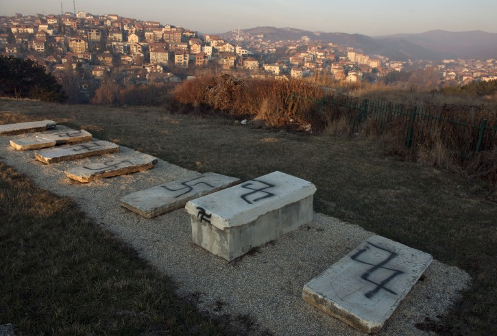 Swastikas sprayed on top of tombstones in a Jewish cemetery promoting police to launch an investigation in to the act of vandalism in the capital Pristina, Kosovo on Thursday, Dec. 1, 2011. ( AP Photo / Visar Kryeziu )