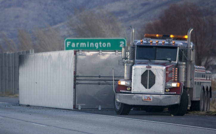 A tipped semi truck lies along the shoulder of I-15 northbound near Farmington, Utah, on Thursday, Dec. 1, 2011  High winds ripping through Utah have overturned several semi-trucks, knocked out power to more than 50,000 customers and prompted school closures.  (AP Photo/The Salt Lake Tribune, Al Hartmann)