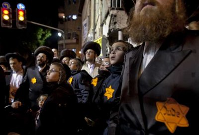 """Ultra-Orthodox Jews wearing yellow Stars of David with 'Jude"""" written on them during a protest in Jerusalem's Mea Shearim neighborhood, 31 December 2011, protesting what they call the 'media campaign of incitement' being waged against their community , especially as it refers to the separation of men and women in the ultra-Orthodox Jewish society.  EPA/JIM HOLLANDER"""