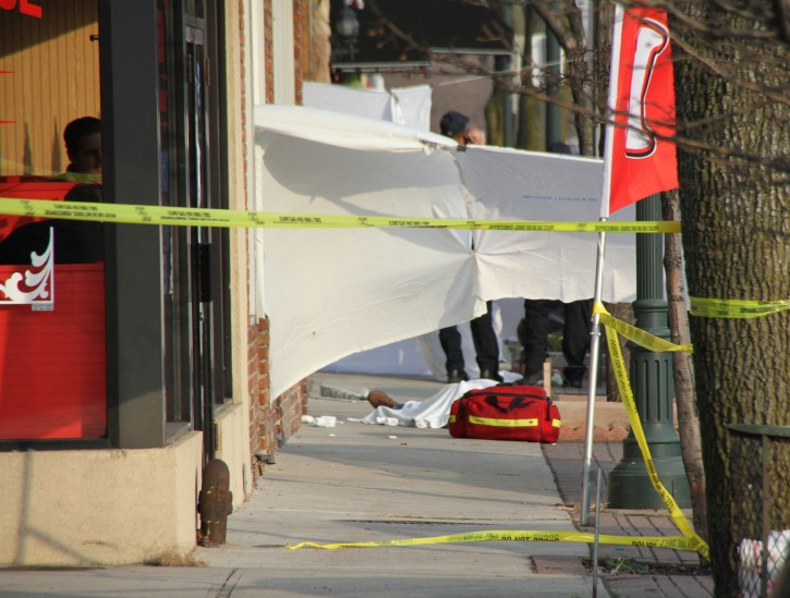A sheet covers a body after a shooting at a pharmacy, Saturday, Dec. 31, 2011, in Seaford, N.Y. A man who police say robbed a pharmacy was shot and killed in a confrontation outside the Long Island store as he was leaving. Nassau County police said the unidentified man entered the pharmacy and announced a robbery, then exited with cash and drugs. Three people intervened as the man left the shop, police said. The Bureau of Alcohol, Tobacco, Firearms and Explosives identified the fallen agent as 51-year-old John Capano, a 23-year veteran of the agency. (AP Photo/Nick Stein)