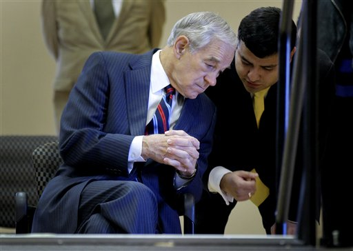 Republican presidential candidate ,Rep. Ron Paul, R-Texas, talks with an aide before speaking to a members of the group Hispanics in Politics, Wednesday, Feb. 1, 2012, in Las Vegas.  (AP Photo/Julie Jacobson)