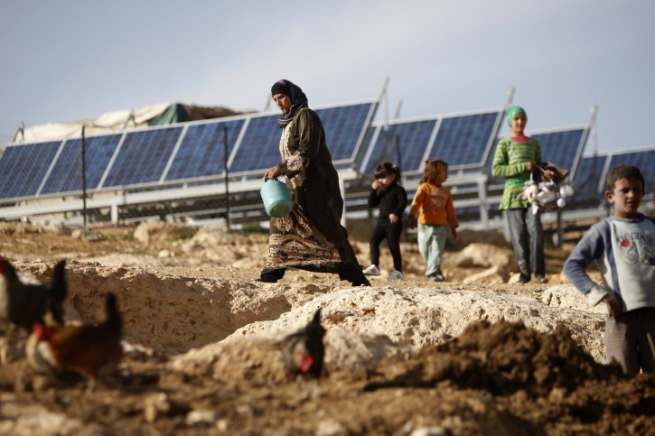 In this photo taken Wednesday, Feb. 22, 2012, a Palestinian woman and children walk in front of solar panels in the Al-Thala community, north of the West Bank city of Hebron. Electricity from solar panels and wind turbines has revolutionized life in Palestinian herding communities that Israel won't connect to the grid: machines instead of sticks churn goat milk into butter, refrigerators store food that used to spoil and children no longer have to hurry to get their homework done before dark. (AP Photo/Majdi Mohammed)