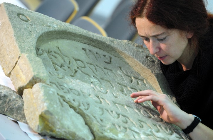 Maria Stuerzebecher, Erfurt's commissionar for UNESCO?World Heritage, examines a Jewish tombstone from 1259 in Erfurt, Germany, 08 February 2012. It is the oldest existing Jewish tombstone in Erfurt to date. It was found a few weeks ago during construction works in the city.  EPA/MARTIN SCHUTT