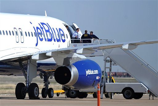 Authorities board JetBlue flight 191, which was headed from New York to Las Vegas, after an emergency landing at Rick Husband Amarillo International Airport in Amarillo, Texas, Tuesday, March 27, 2012, when an unruly pilot caused the Las Vegas-bound flight to be diverted. Passengers said the pilot screamed that Iraq or Afghanistan had planted a bomb on the flight, was locked out of the cockpit, and then tackled and restrained by passengers. The pilot who subsequently took command of the aircraft elected to land in Amarillo at about 10 a.m., JetBlue Airways said in a statement. (AP Photo/The Amarillo Globe News, Roberto Rodriguez)