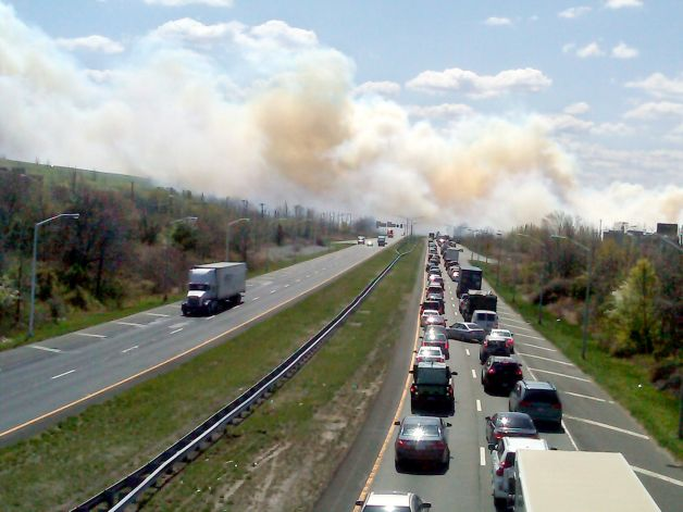 Traffic grinds to a halt as a smoky brush fire jumps the highway and closes one of the main traffic arteries on the Staten Island borough of New York, Monday, April 9, 2012. Over 100 firefighters battled the blaze that started in Great Kills Park. Photo: Staten Island Advance, Jan Somma-Hammel / AP