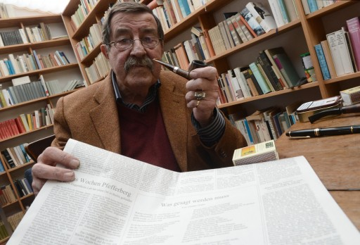 Nobel Prize for Literature laureate Guenter Grass sits in his study and holds up his controversial Israel poem in Behlendorf, Germany, 05 April 2012.
