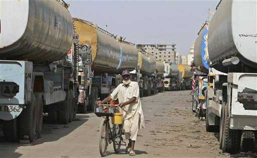 A Pakistani man selling cold drinks pushes his bicycle between oil tankers, which were used to transport NATO fuel supplies to Afghanistan, in a compound in Karachi, Pakistan, Thursday, May 24, 2012. (AP Photo/Fareed Khan)