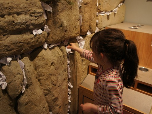 A girl puts a note in the wall at Crown Heights' Jewish Children's Museum. The Museum recently unveiled its (eminently climbable) Voyage Through Jewish History, which takes pint-sized visitors through stories of the bible to the contemporary age. PHOTO CREDIT DNAinfo/Sonja Sharp