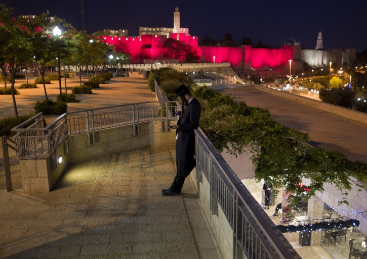 An ultra-Orthodox Jewish man uses his mobile phone on a promenade before the Jaffa Gate and Tower of David area of the Old City walls of Jerusalem, bathed in pink light, in Jerusalem, Israel, 01 May 2012. Jerusalem's Old City walls for the second year in a row are lit in pink to increase awareness in finding a cure for breast cancer. The Susan Komen 'Race for the Cure' will be held in Jerusalem on 03 May.  EPA/JIM HOLLANDER
