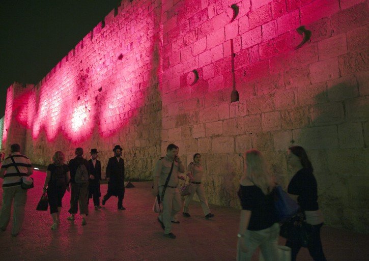 Ultra-Orhtodox Jews, Israeli soldiers and pedestrians walk along the Old City walls of Jerusalem near the Jaffa Gate, bathed in pink light, in Jerusalem, Israel, 01 May 2012. Jerusalem's Old City walls for the second year in a row are lit in pink to increase awareness in finding a cure for breast cancer. The Susan Komen 'Race for the Cure' will be held in Jerusalem on 03 May.  EPA/JIM HOLLANDER