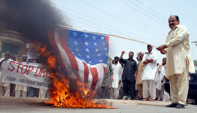 People burn a mock US flag as they shout slogans during a protest against US drone attacks, in Multan, Pakistan, 25 May 2012. EPA