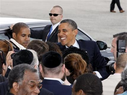President Barack Obama shakes hands to a group people at JFK International Airport in New York, Monday, June, 4, 2012, on his way to a visit in New York City. (AP Photo/David Karp)
