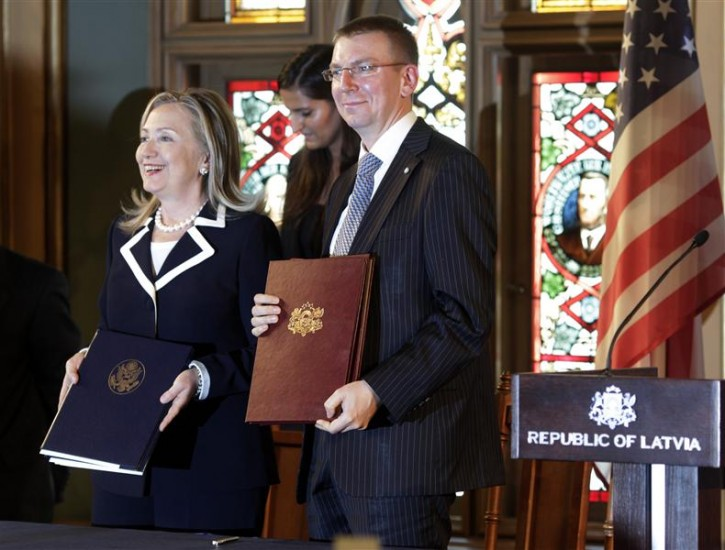 U.S. State Secretary Hillary Clinton (L) and Latvia's Minister of Foreign Affairs Edgars Rinkevics pose for media with the signed documents in Riga June 28, 2012. Clinton is on one day visit to Latvia. REUTERS/Ints Kalnins