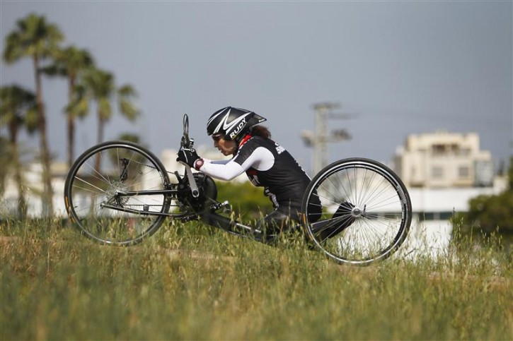Pascale Bercovitch rides her hand bike during a training session in a park in Tel Aviv May 14, 2012. Bercovitch, 44, who lost her legs in a train accident in France in 1984, will represent Israel at the London Paralympics in hand cycling events. Picture taken May 14, 2012.   REUTERS/Nir Elias