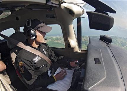 In this June 27, 2012 photo, Ohio State Highway Patrol trooper Bryan Dail hunts for speeders from an aircraft over Ohio Route 2 near Vermilion, Ohio. While Ohio still aggressively uses aircraft to catch speeders, many states have cut back or eliminated aerial enforcement due to budget concerns. (AP Photo/Mark Duncan)