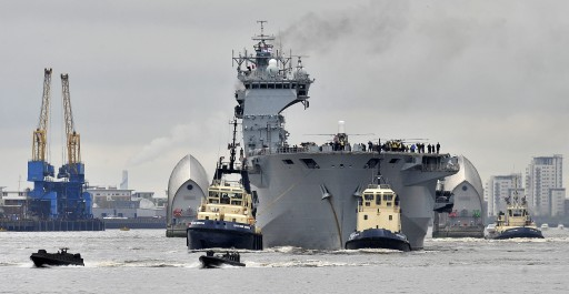 FILE - The British Royal Navy's largest ship HMS Ocean sails up the River Thames past the Thames Barrier in London  04 May 2012 escorted by a flotilla of smaller vessels. The Ocean was heading for Greenwich  where it will act as a launch pad for helicopters during a major security exercise in preparation for the Olympic Games, called Olympic Guardian.  EPA/ANDY RAIN