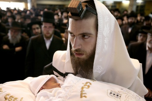 File photo of an ultra orthodox Chassidic father holds his baby at a Brit milah. Photo by Abir Sultan/Flash90
