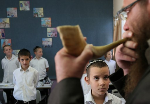"""Young students watch as their teacher blow a shofar in the classroom of the """"Talmud Torah Ohalei Menachem"""" school in the ultra orthodox Jewish settlement of Beitar Illit. August 19, 2012. Photo by Nati Shohat/Flash90."""