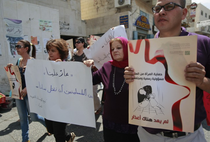"Palestinian women hold signs in Arabic that read, ""protecting women from violence is an official (authorities) and social responsibility,"" right, and ""shame on us. We Palestinians for killing our women,"" left, during a demonstration protesting violence against women held at the spot where a woman's throat was allegedly slashed by her husband on Monday, in the West Bank town of Bethlehem, Wednesday, Aug. 1, 2012. Dozens of activists called on police and courts to do more to protect women against abusive husbands. Palestinian President Mahmoud Abbas has promised to end a long-standing practice of treating killings in the family 'with leniency. However, violence against women continues to be tolerated in Palestinian society and abusive husbands are rarely punished. (AP Photo/Majdi Mohammed)"