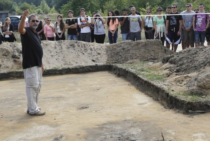 Israeli archaeologist Yoram Haimi ,left, talking to young people from the Dror School in Israel about his findings at the site of the former German Nazi death camp of Sobibor, in eastern Poland, on Tuesday, Aug. 21, 2012.  Dror  school is trying to find remains of the camp still hidden in the ground in order to redraw its shape. The Nazis burned the camp to the ground  in  to erase all trace of it as the Soviet Red Army was approaching.   (AP Photo/Czarek Sokolowski)