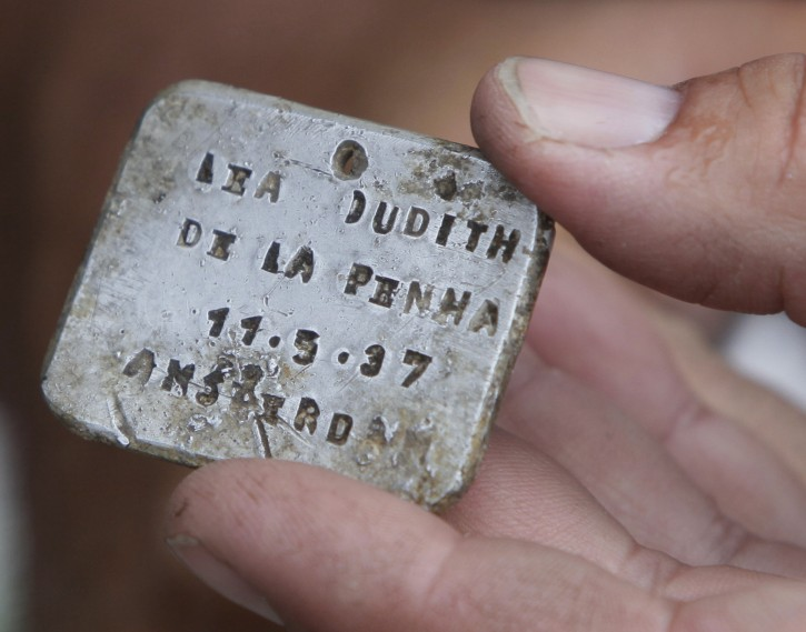 Israeli archaeologist Yoram Haimi shows aluminum plate to young people from Dror  school  in Israel  at the site of the former German Nazi death camp of Sobibor, in eastern Poland, on Tuesday, Aug. 21, 2012.  Dror  school is trying to find remains of the camp still hidden in the ground in order to redraw its shape. The Nazis burned the camp to the ground  in  to erase all trace of it as the Soviet Red Army was approaching.   (AP Photo/Czarek Sokolowski)