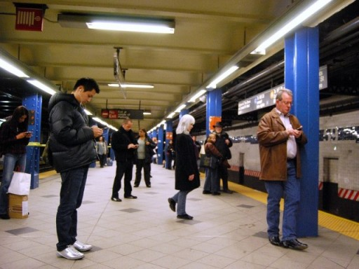 Straphangers use their mobile devices on the subway platform. Cellular and WiFi service is being planned for underground. (Paul Lowry/Flickr)