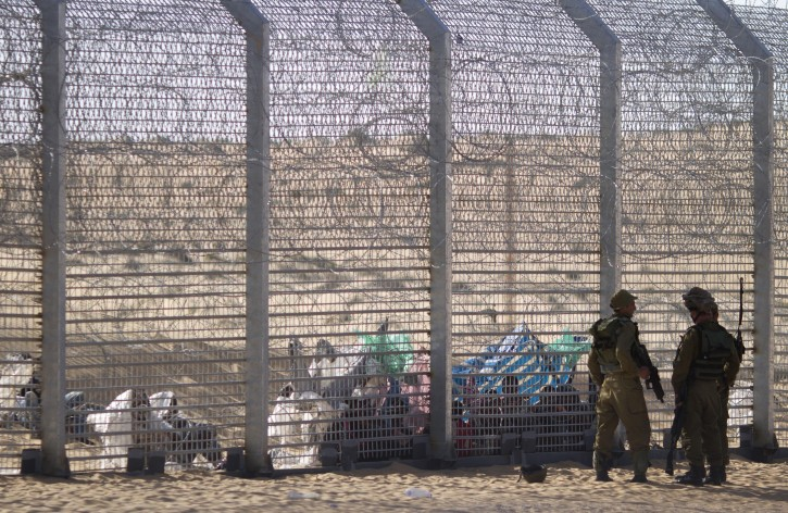 African refugees sit on the ground behind a border fence after they attempted to cross illegally from Egypt into Israel as Israeli soldiers stand guard near the border with Egypt, in southern Israel, Tuesday, Sept. 4, 2012. Israel is staunching the flow of African migrants who have poured into the Jewish state by the tens of thousands, rapidly building a border fence and implementing a new policy of detaining Africans upon arrival. Israel's army says over the past few days, a group of African migrants has waited on the Egyptian side of the fence. Israeli soldiers are providing the group with water, but not allowing them into Israel.(AP Photo/Ariel Schalit)