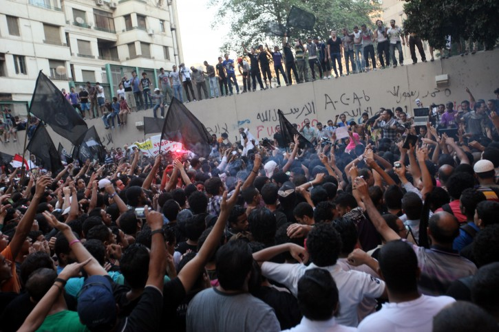 Egyptian protesters protest in front the US embassy, in Cairo, Egypt, 11 September 2012. Egyptian Islamists, angered by a film they say defames Prophet Mohammed, scaled the walls of the US embassy in Cairo in an unprecedented security breach.    Several protesters climbed up onto the walls of the embassy, tore down the US flag, and raised a black flag, before they were removed by security reinforcements who were rushed to the area.  EPA/KHALED ELFIQI