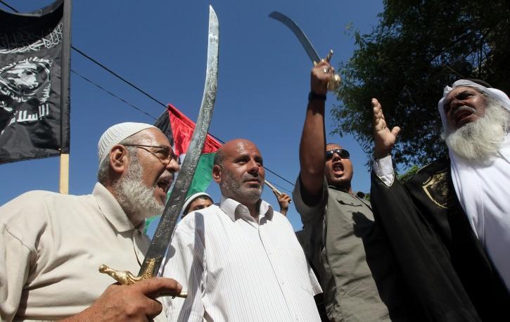 Palestinian muslims chant anti-US slogans while holding up swords during a protest in front the UNSCO headquarter in Gaza City on 12 September 2012. Palestinian muslims burned a US flag during a protest against what they said was a film produced in the United State and that the protesters claim insulted Prophet Mohammed. The film, Innocence of Muslims, which had hardly been heard of before Tuesday, was made by US-Israeli real estate developer Sam Bacile.  EPA/MOHAMMED SABER