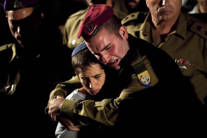 Israeli soldiers, one hugging the little brother of late soldier Netanel Yahalomi, attend his funeral at the military cemetery in Modiin, Israel, 23 September 2012 . Netanel Yahalomi was  killed on 21 September 2012 during a shootout between the Islamic Jihad movement and the Israeli Defence Forces (IDF) soldiers at the Israel-Egypt border.  EPA/ABIR SULTAN