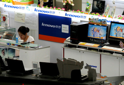 A sale woman works beside a row of Lenovo desktop computer at a shop in Shenzhen, Guangdong province, southern China, 06 August 2009.