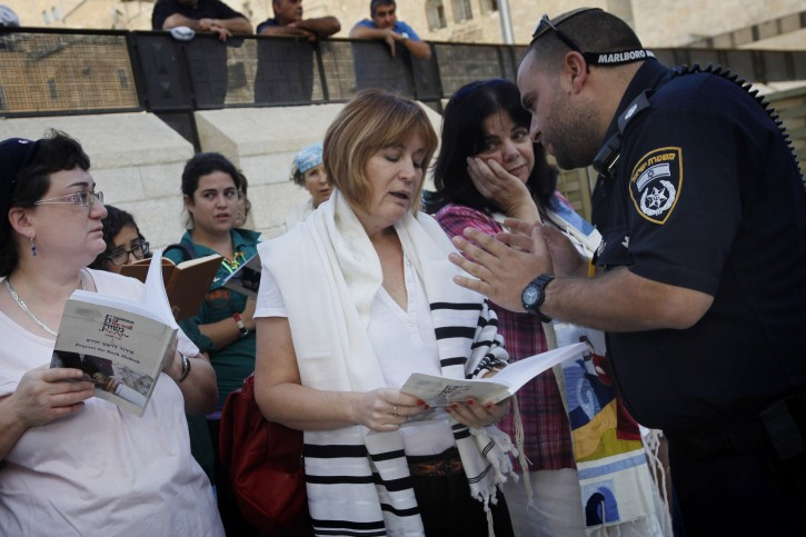 """Lesley Sachs, director of """"Women of the Wall"""" argues with  police due to her wearing a 'tallit' (prayer shawl) visible while morning prayers together with """"WOW"""" at the Western Wall, Judaism's holiest site, in Jerusalem on October 17, 2012. """"Women of the Wall"""" fights for the right for Jewish women to conduct prayer services, read from a Torah scroll while wearing prayer shawls, and sing out loud at the women's section of the Western Wall. Photo by Miriam Alster/FLASH90"""