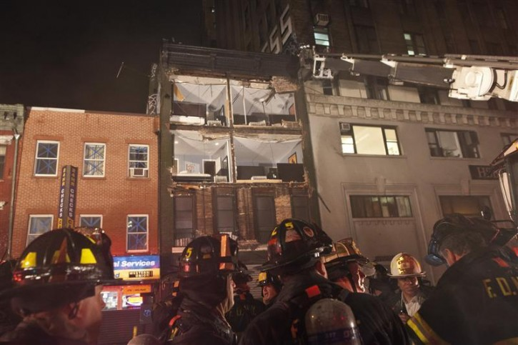 Fire fighters gather in front of a partially collapsed four-storey apartment building in Manhattan as Hurricane Sandy made its approach to New York October 29, 2012. The building's facade had collapsed after high winds had hit New York City. No one was injured in the 25-unit building, according to media reports. REUTERS/Andrew Kelly
