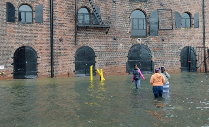 Three friends make their way along a flooded street as the beginning effects of Hurricane Sandy are felt in the Red Hook neighborhood of Brooklyn, New York, USA, 29 October 2012. The storm is one of the largest to hit the region in decades and threatens to cause massive problems for millions of people.  EPA/JUSTIN LANE
