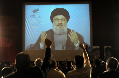 FILE - Supporters of Hezbollah react as they listen to Secretary General of Hezbollah Sayyed Hassan Nasrallah (seen on screen) delivering a speech via video link from an undisclosed location, as they gather at Unesco palace in Beirut, Lebanon, 01 June 2012.
