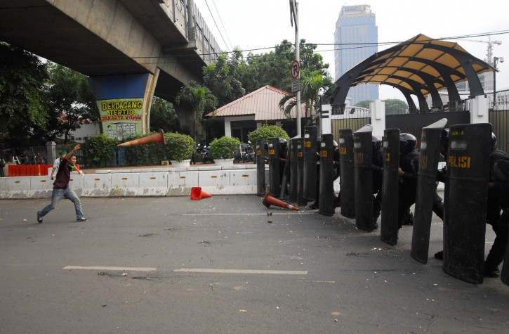 An Indonesian student protester throws a traffic cone at riot police in a brief clash during a protest against Israel's attack on Gaza, outside the U.S. Embassy in Jakarta, Indonesia, Wednesday, Nov.21, 2012. (AP Photo)