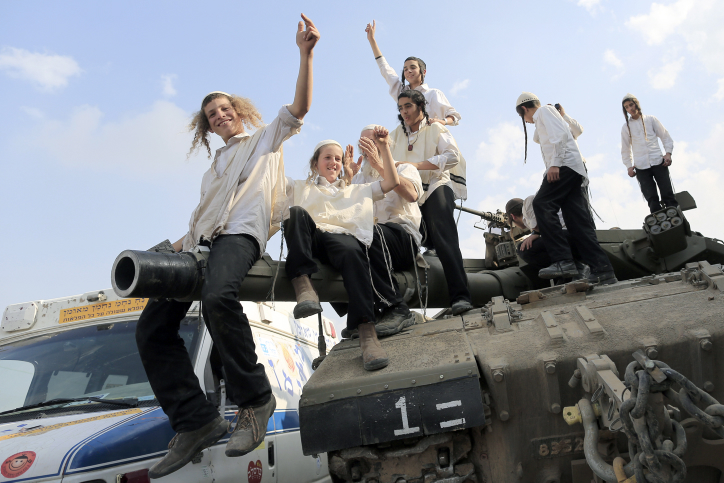 Ultra-Orthodox Jews of the Bratslav Hasidic sect, that gathered to show support for the forces, dance as they celebrate atop of a tank in southern Israel, close to the Israel Gaza Strip Border, Thursday, Nov. 22, 2012. Photo by Tsafrir Abayov/Flash90