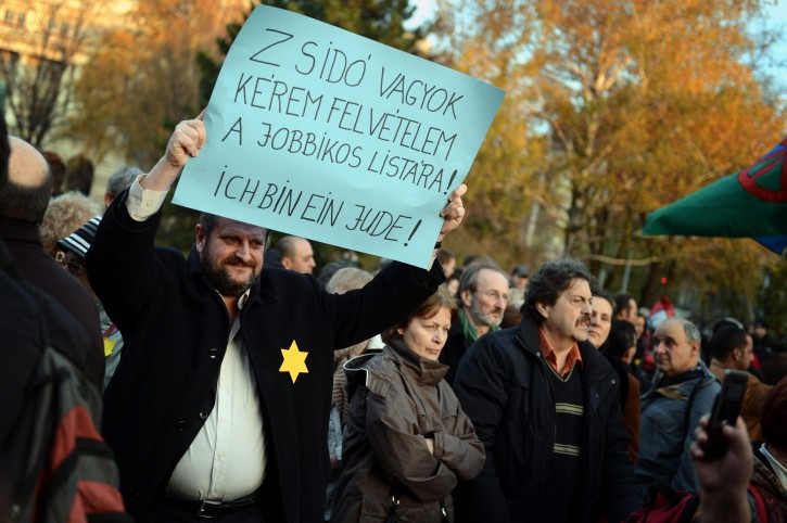 "A demonstrator holds a placard as he wears a yellow star during the protest against the speech held by Marton Gyongyosi, a deputy of the far-right Jobbik party on Monday in front of the Parliament building in Budapest, Hungary, Tuesday, Nov., 27, 2012. The banner reads: ""I am a Jew. Please, include my name on the Jobbik-list"". The demonstration was organized by the March of The Living Foundation. (AP Photo/MTI, Tamas Kovacs)"